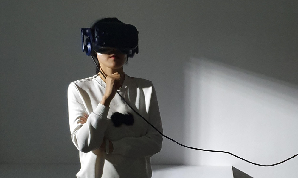 Girl using VR goggles for The Edge of the Present immersive experience photo credit - Jessica Maurer